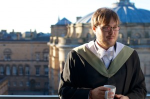 Young man with beard and graduation gown drinking tea