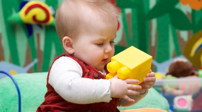 Baby playing with a yellow mega bloc